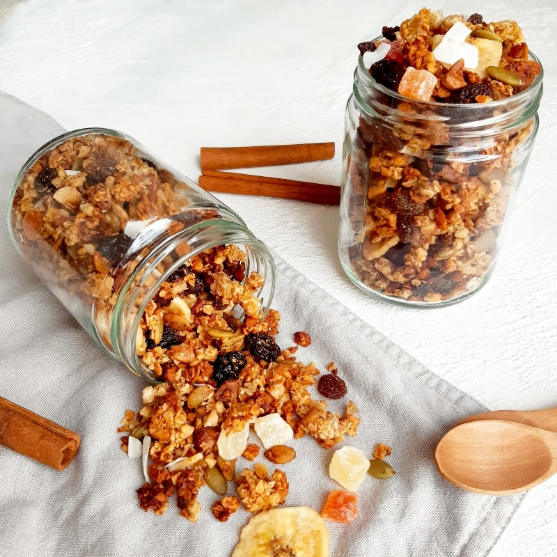 Glass jar tipped over with heathy granola spilling out.
