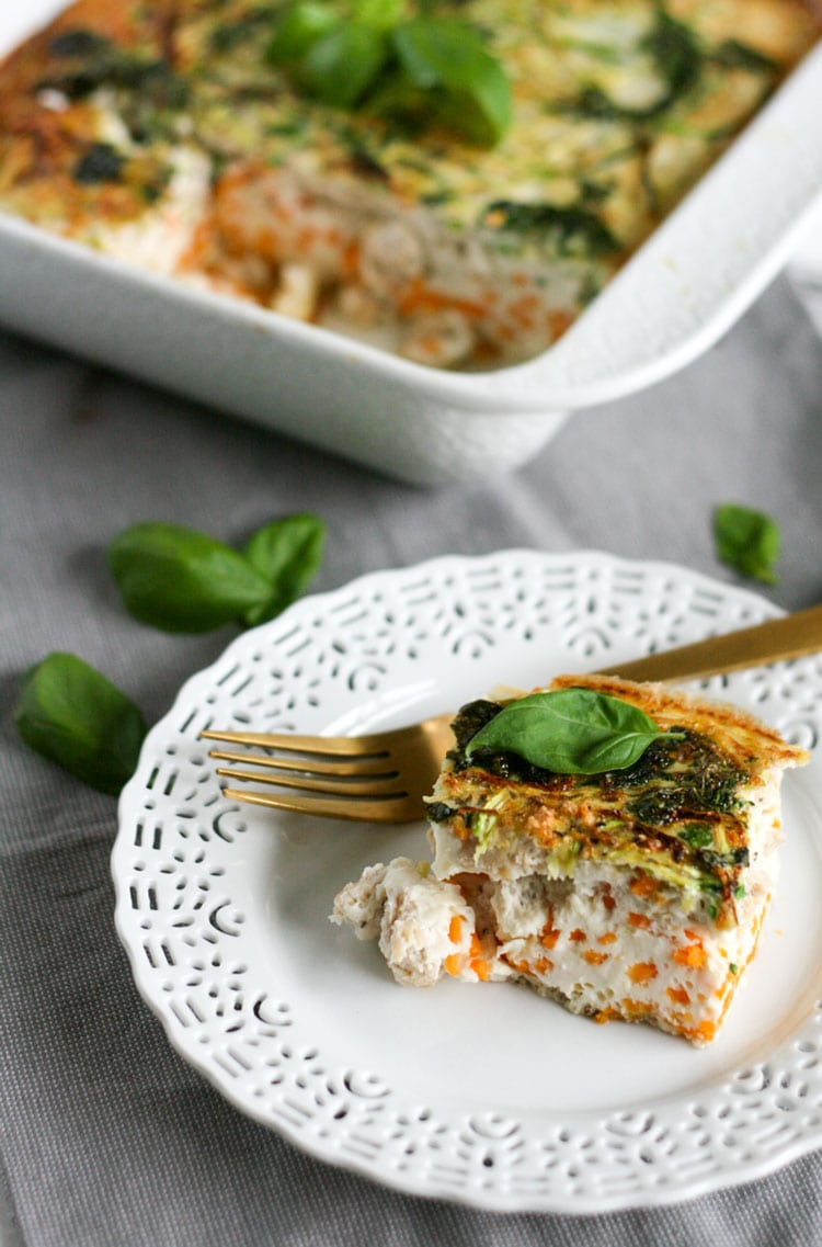 Healthy breakfast casserole on a white plate with golden fork.