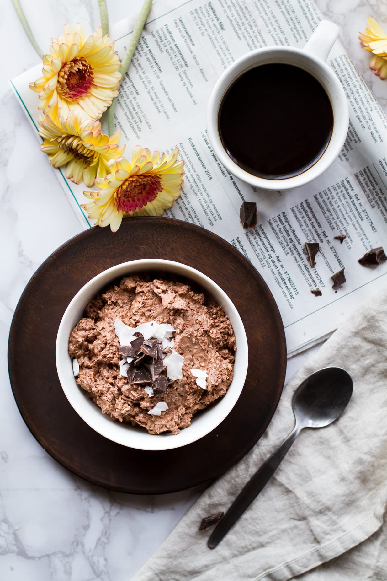 White bowl with chocolate coconut overnight oats on a wooden plate.