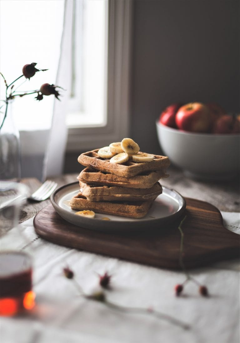 A stack of healthy breakfast waffles on a plate. Apples in the background.