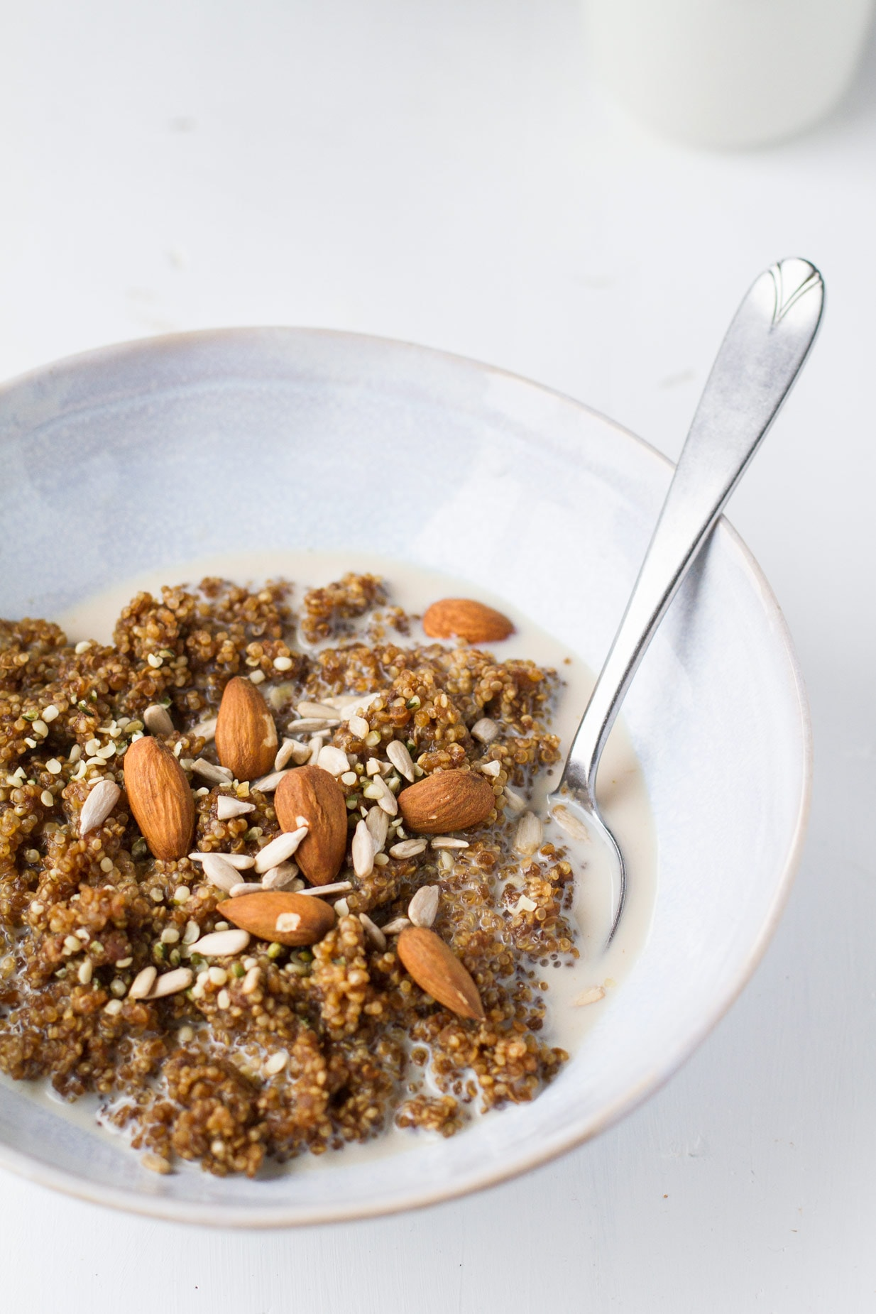 A blue bowl with breakfast quinoa and milk, topped with sunflower seeds and almonds.