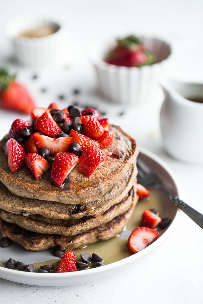 A stack of healthy buckwheat chocolate pancakes, topped with strawberries.