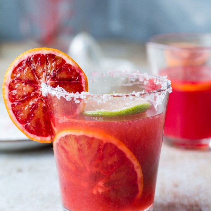 Close-up of one glass with blood orange margarita, garnished with blood orange on the side and in the drink.