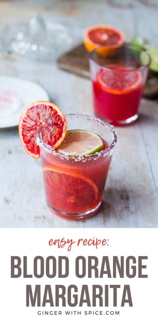 Glass with blood orange margarita, slices of blood oranges and salted rim. Pinterest pin.