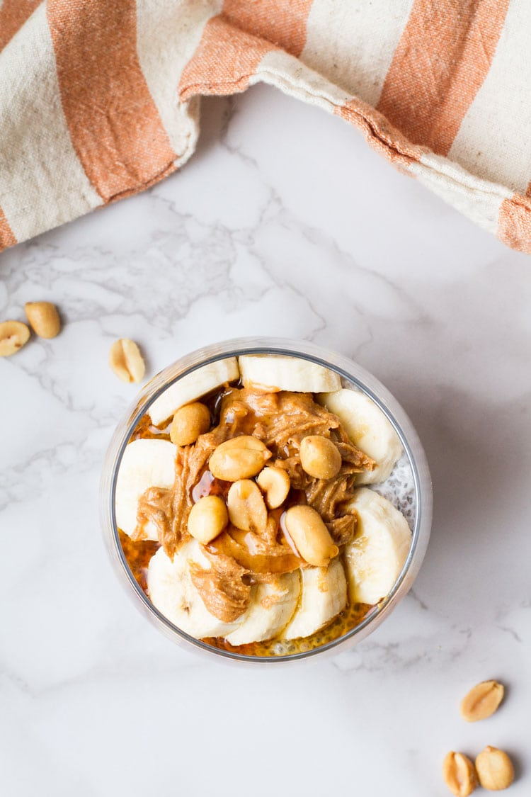 Glass with slices of banana, peanut butter, salted peanuts and maple syrup. White background, flatlay.