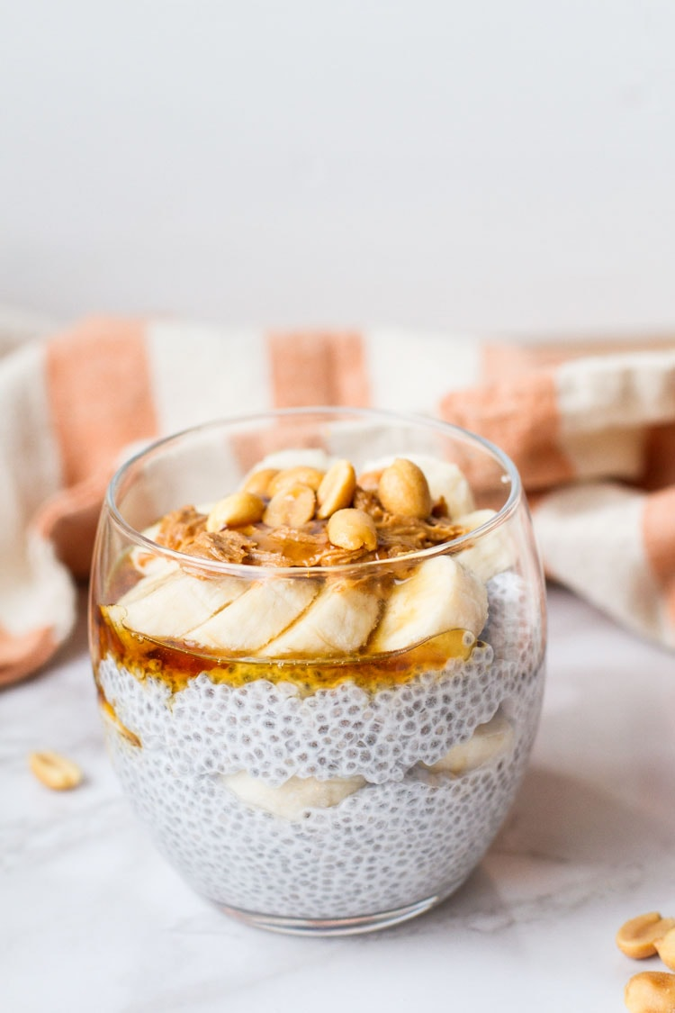 Round glass with chia pudding topped with sliced banana, peanut butter and peanuts. White background.