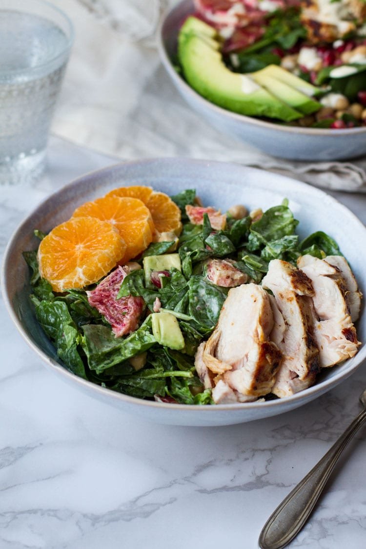 A blue bowl with spinach salad topped with sliced chicken and clementine.