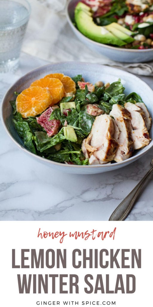 A blue bowl with spinach salad topped with sliced chicken and clementine. Pinterest pin.