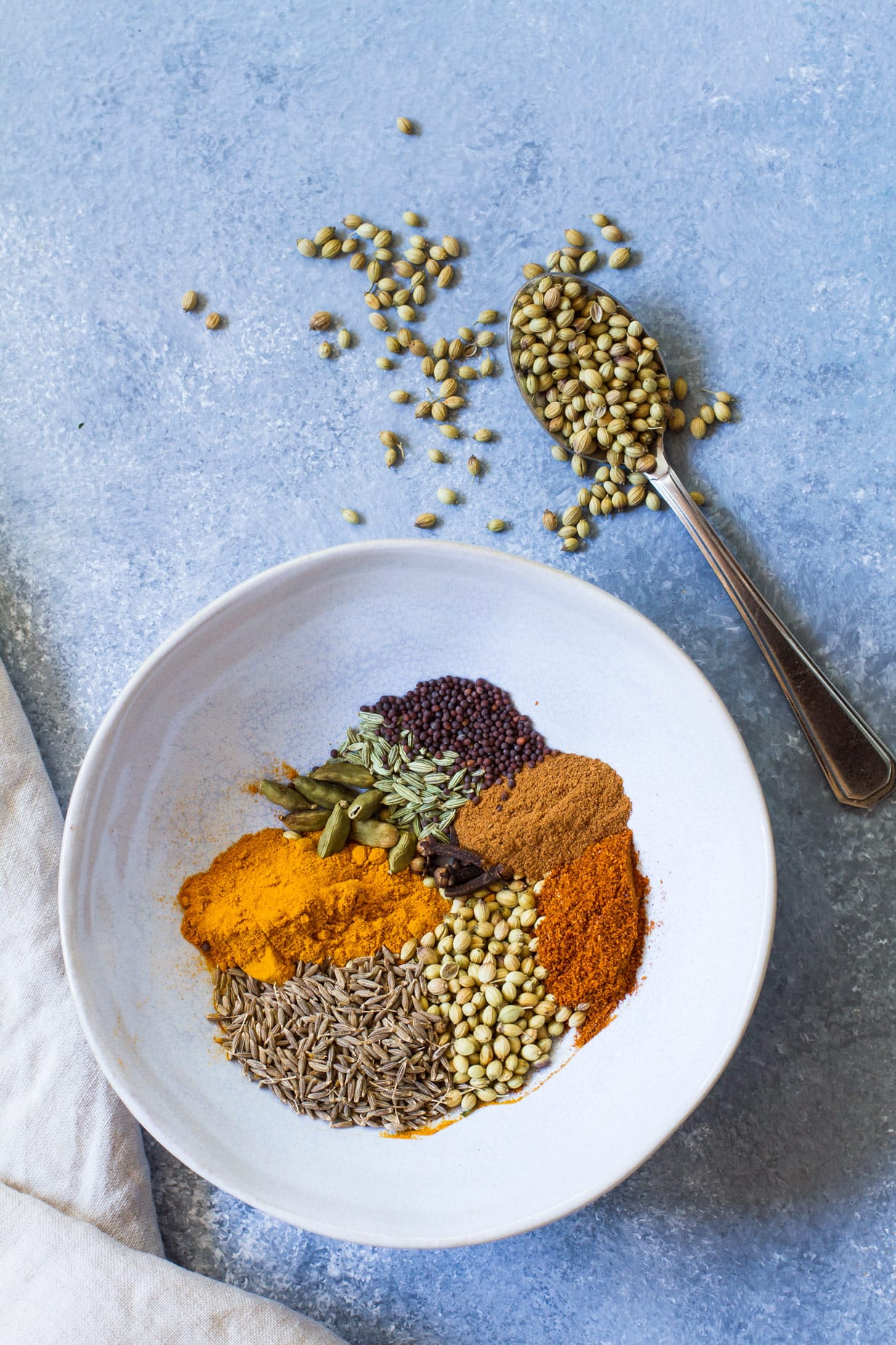 Spices to make curry in a blue bowl on a blue background.