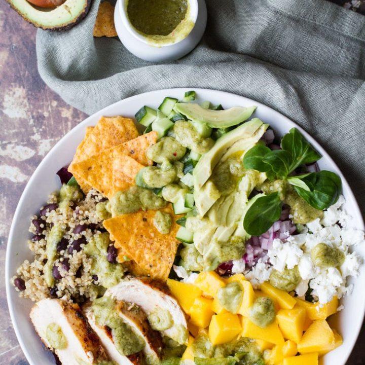 Mango salad with chicken, tortilla chips, avocado and more. Flatlay.
