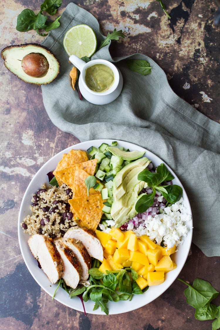 A white bowl with mango, feta cheese, avocado slices, rice and beans and chicken.