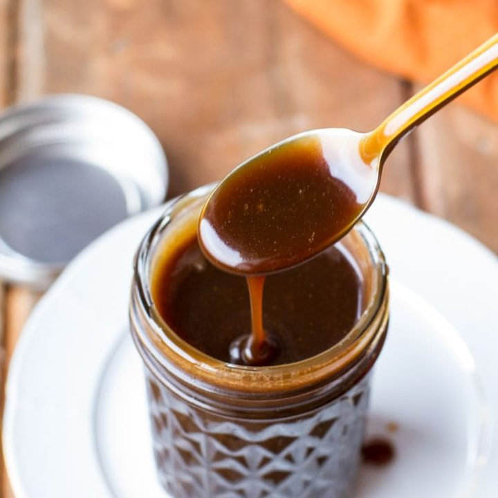 Spoon drizzling Guinness coffee salted caramel sauce into a glass jar.