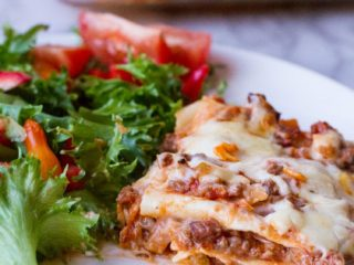 Lasagna and side salad on a white plate.