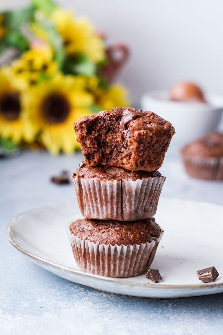 Three chocolate banana muffins on top of each other, top one is taken a bite out of. Sunflowers in the background.