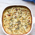 White casserole with scalloped potatoes and a cheesy top. Blue linen on the side.
