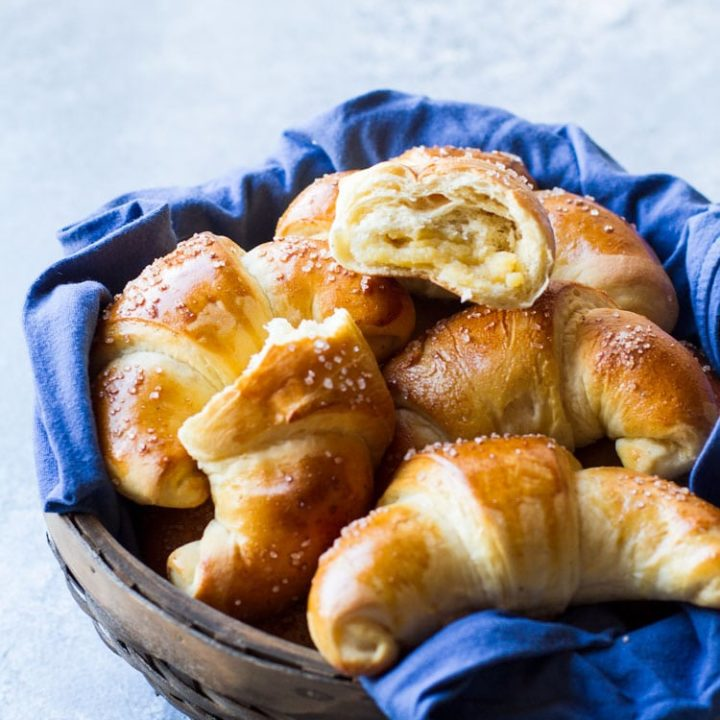 Wooden basket with blue linen and crescent rolls, one open.
