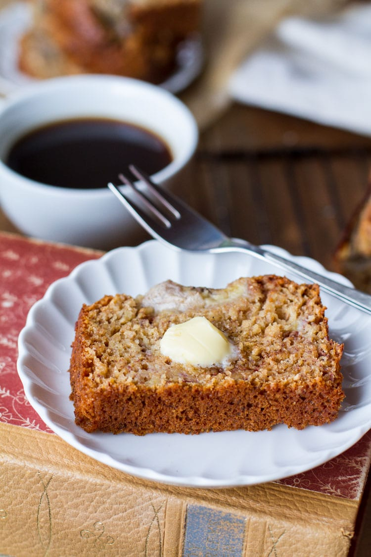 Slice of banana bread with a dollop of butter, coffee in the background.