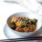 Pork and broccoli stir fry with noodles. Chopsticks on the side.