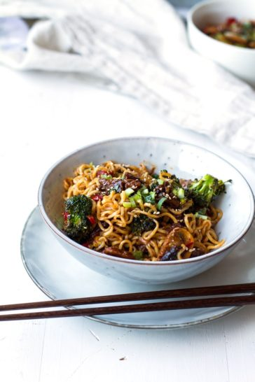 Pork and broccoli stir fry with noodles. Chopsticks on the side.