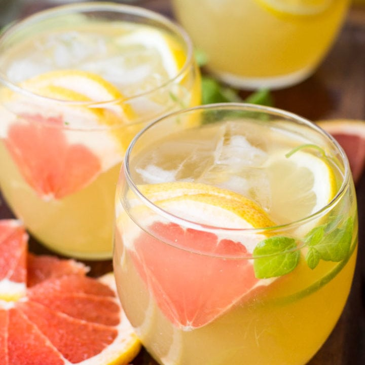 Round glasses with a yellow drink, sliced grapefruit and ice cubes.
