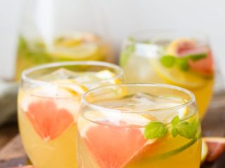 Three glasses with cold tea, ice cubes and sliced grapefruit.