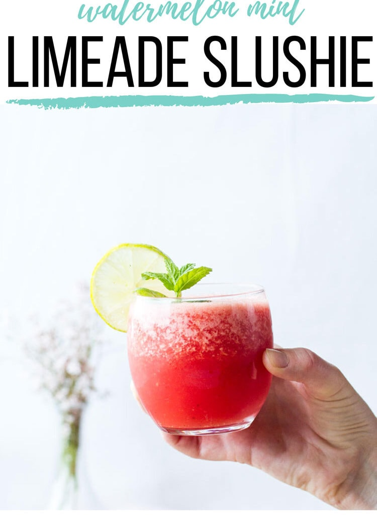 Hand holding a glass of watermelon limeade, garnised with lime and mint. Pinterest pin.