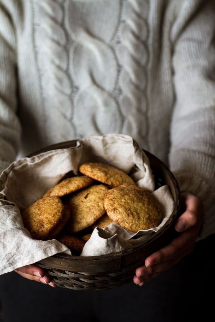 A person in a white woollen sweater, holding a basket of cookies.