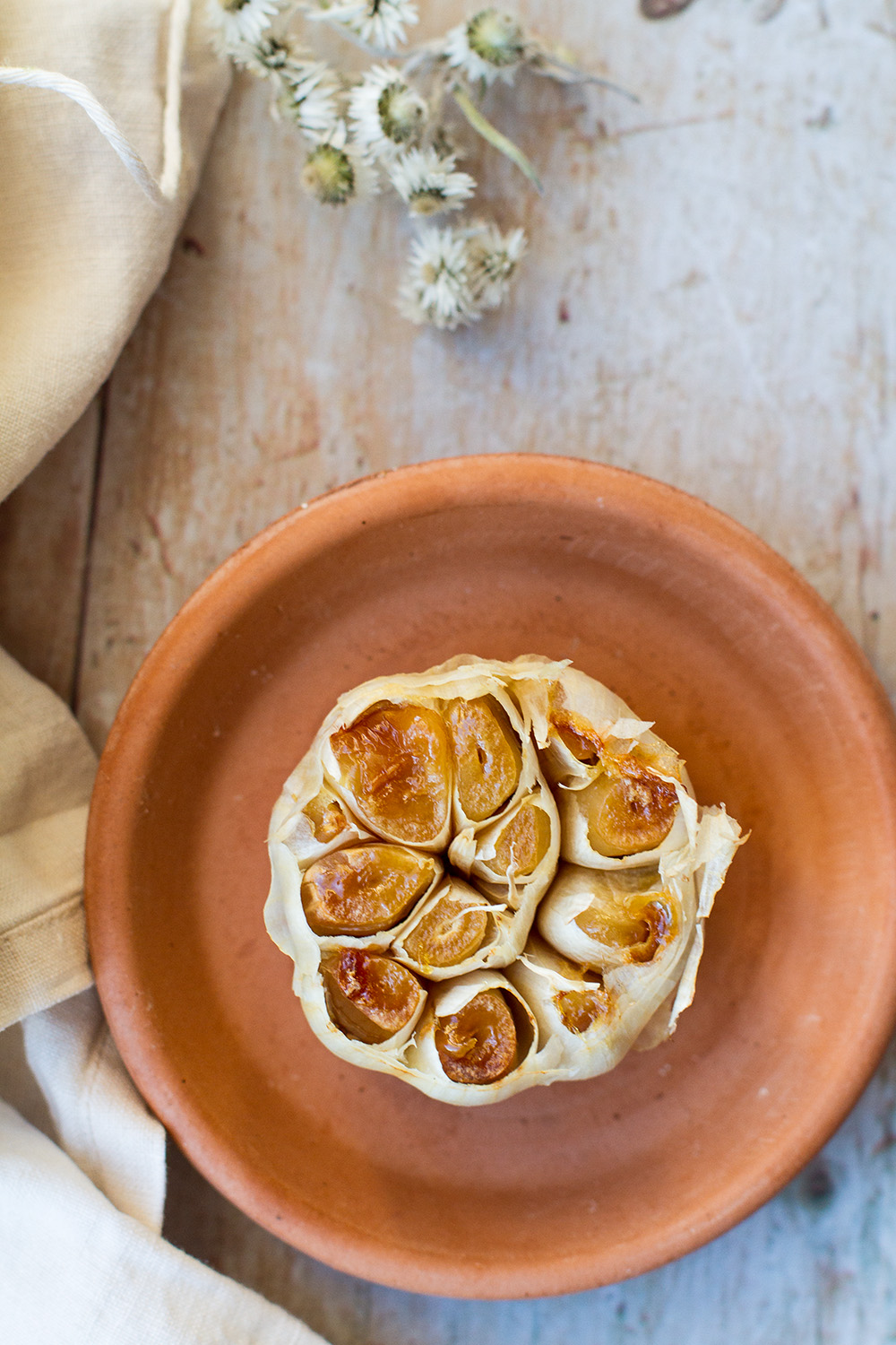 Roasted garlic on a small terracotta plate.