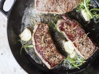 3 striploin steaks in a cast iron skillet with rosemary and garlic.