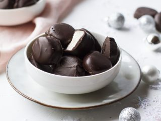 Small white bowl with peppermint patties on a white plate. Decorated with snow flakes and ornaments.