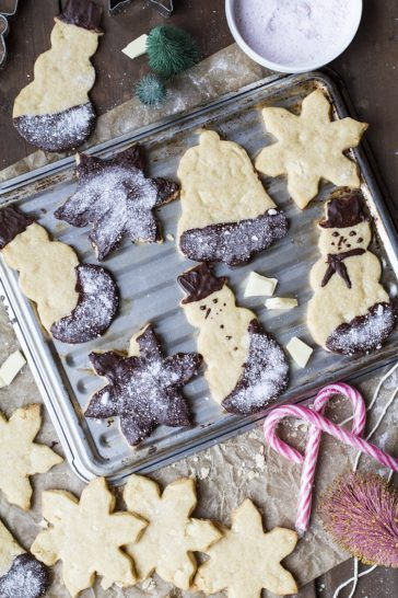 Snowmen shaped and star shaped cookies on a cookie tray. Candy cane decorations. Flat-lay.