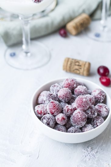 A small white bowl with sugared cranberries.