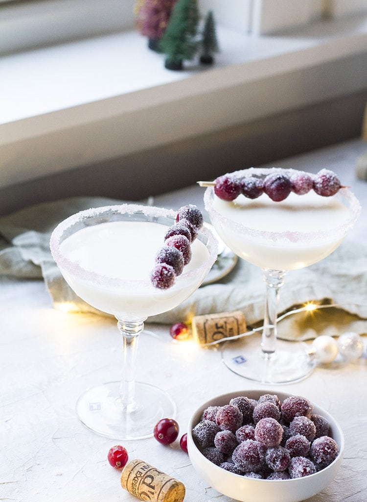 Two coupé glass with a white cocktail and sugar cranberries garnish.