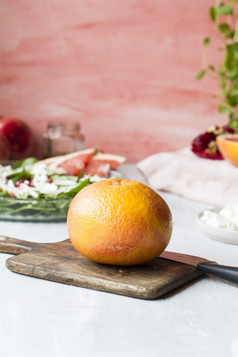 Grapefruit on a cutting board. Pink background.