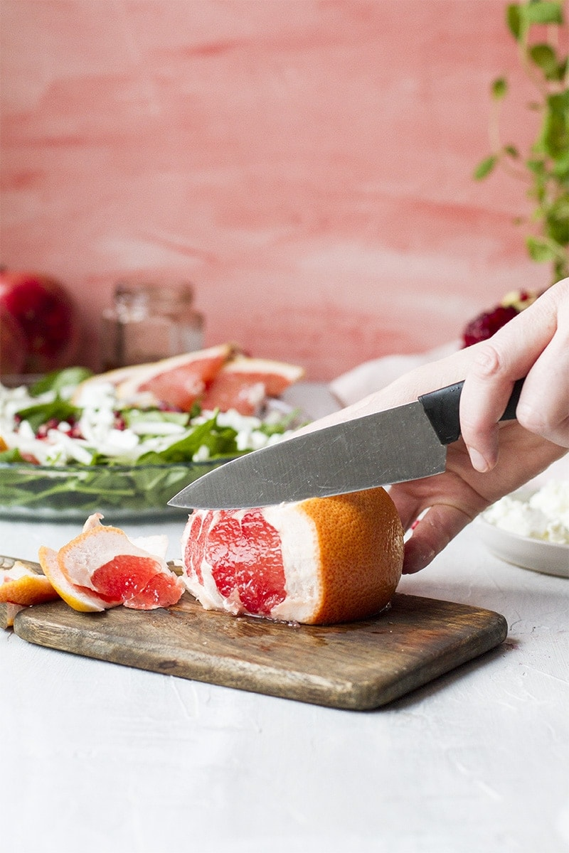 Cutting and peeling a grapefruit on a cutting board.
