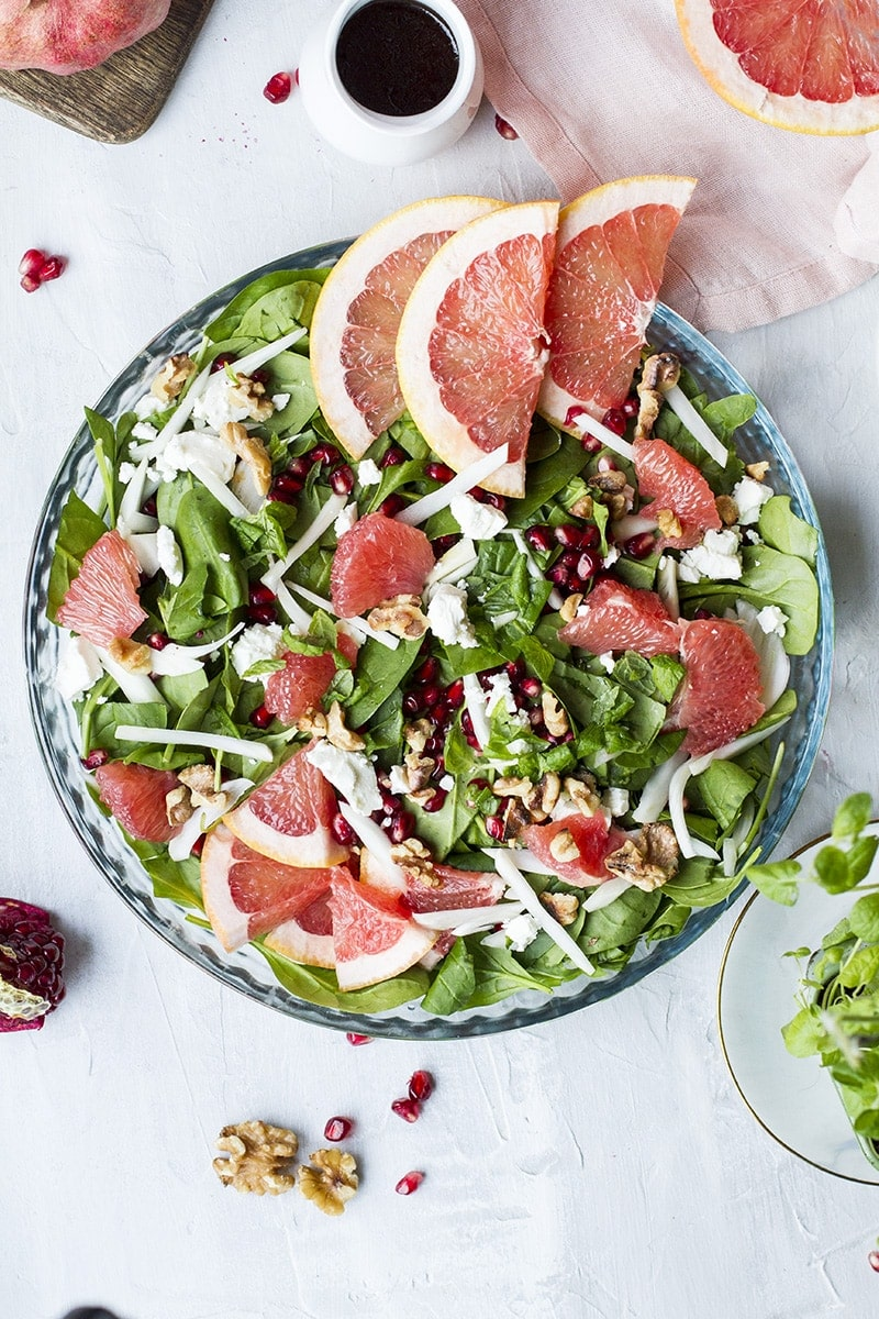 Salad in a shallow pan, seen from above. Garnished with grapefruit slices, fennel and pomegranate.