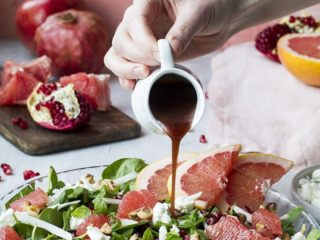 Hand pouring pomegranate vinaigrette over a grapefruit salad in a shallow pan.