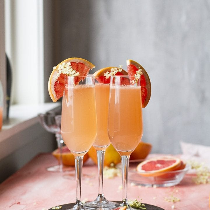 Three grapefruit mimosas in champagne flutes. Pink table.