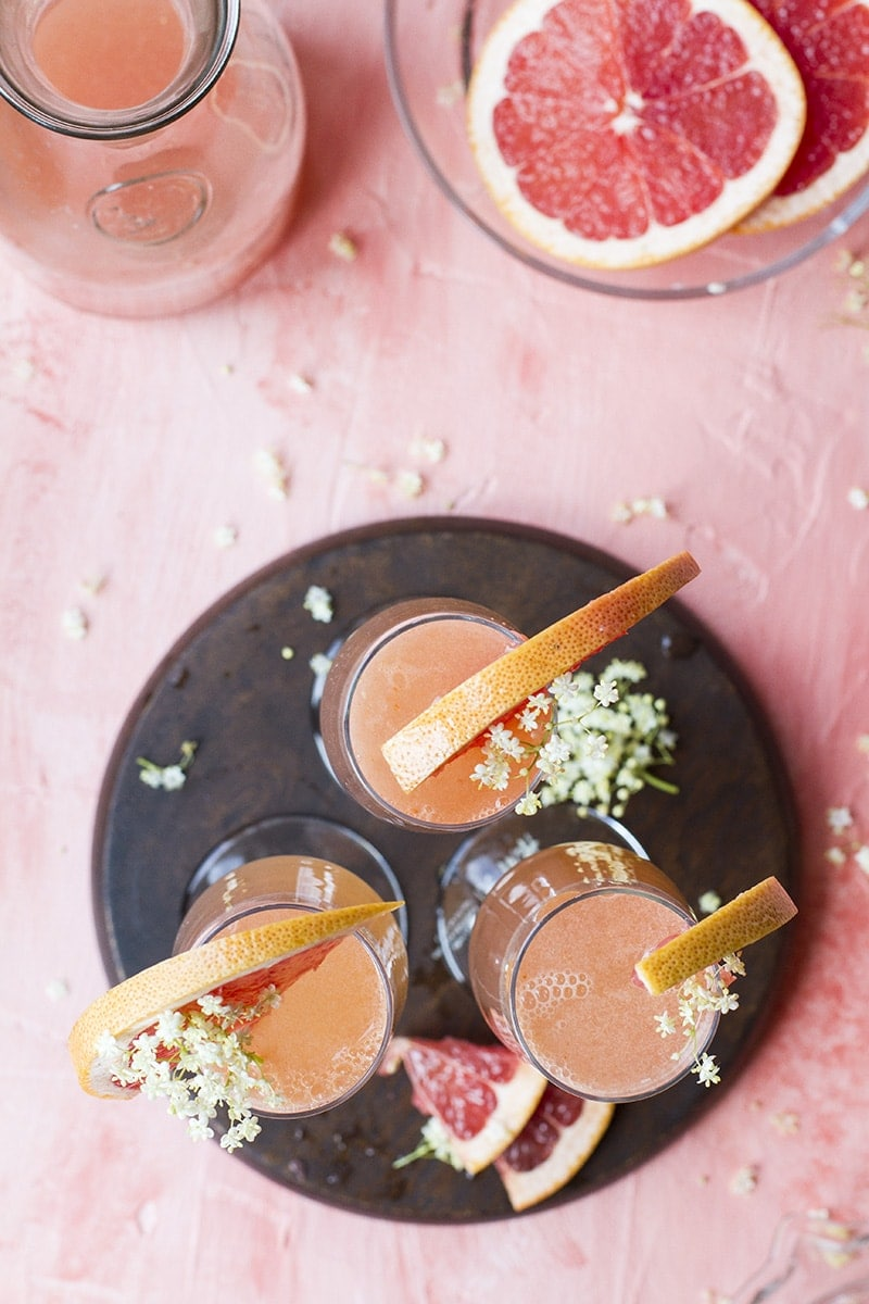 Three champagne flutes seen from above, garnished with grapefruit slices and elderflower.