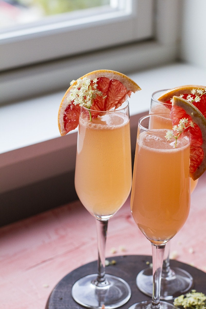 Three grapefruit cocktails in champagne flutes.