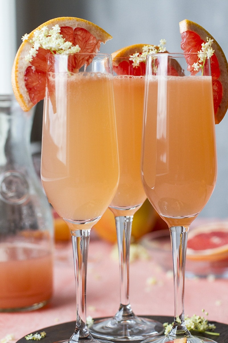 Close-up of three champagne flutes with grapefruit mimosa. Garnished with sliced grapefruit and elderflower.