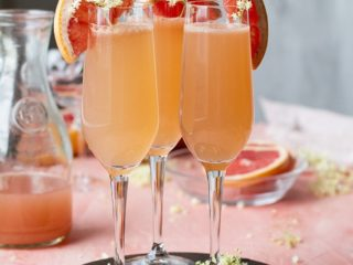 Three champagne flutes with pink mimosa, on a pink table.