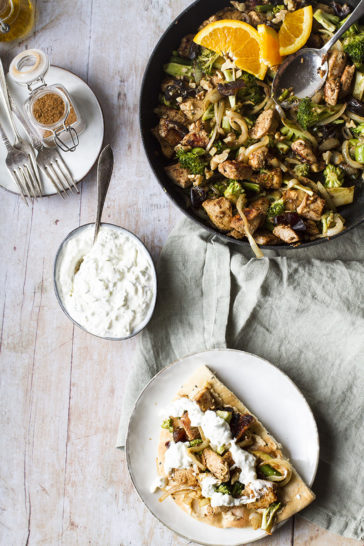 A skillet with shawarma chicken and a plate with a naan and the chicken on top.