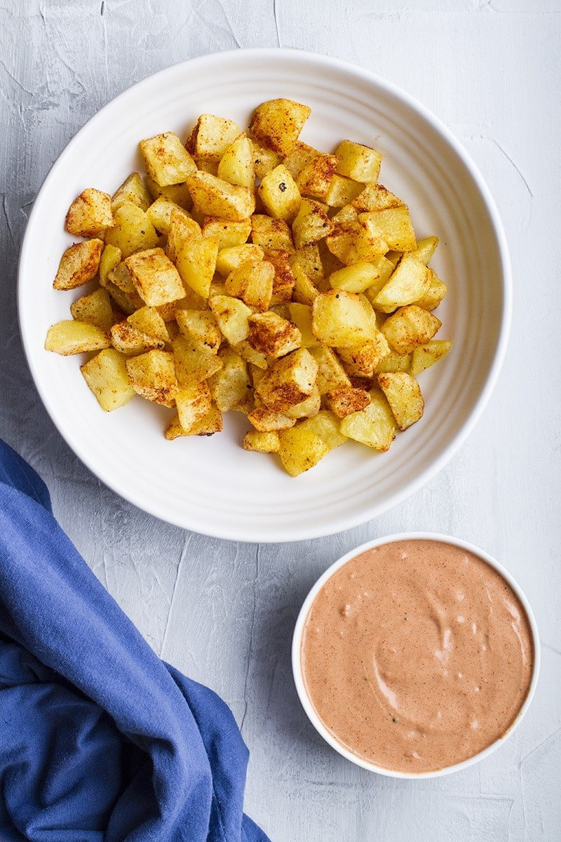 One large dish with cubed fried potatoes and one small with tomato aïoli.