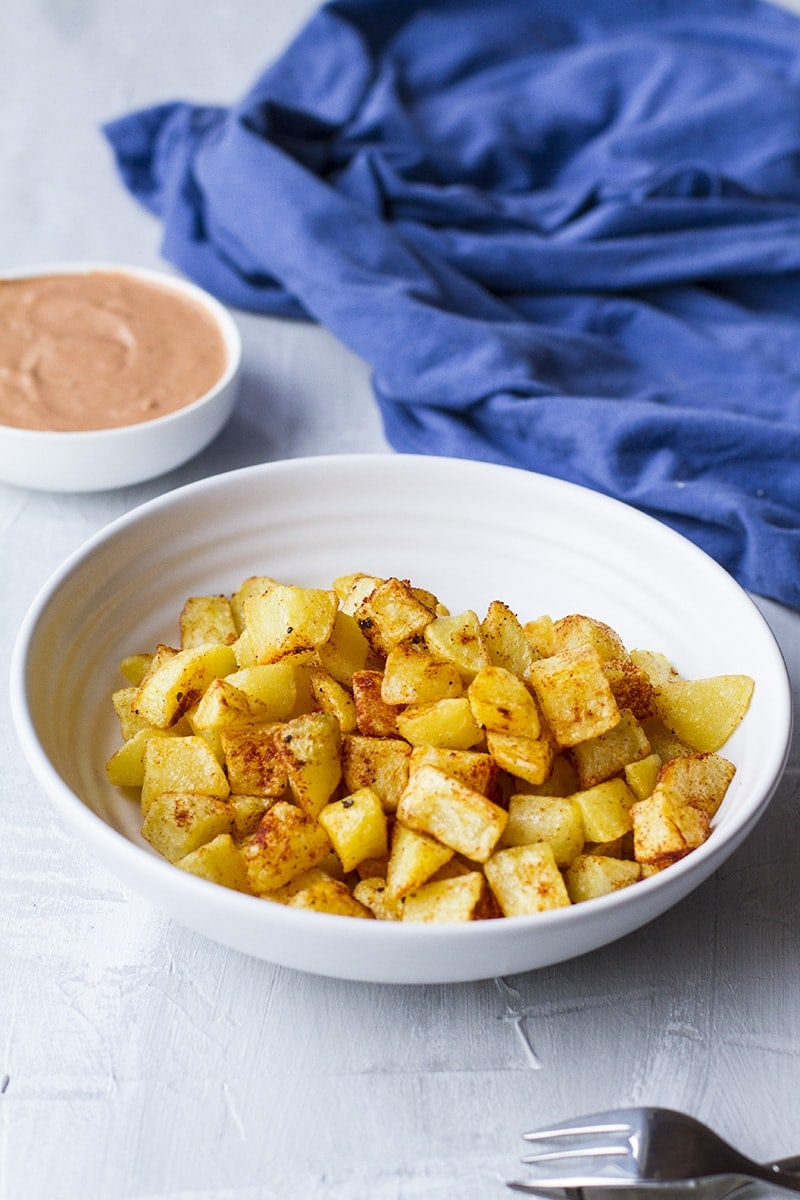 Large white bowl with fried cubed potatoes covered in chili spices. Blue linen in the background.