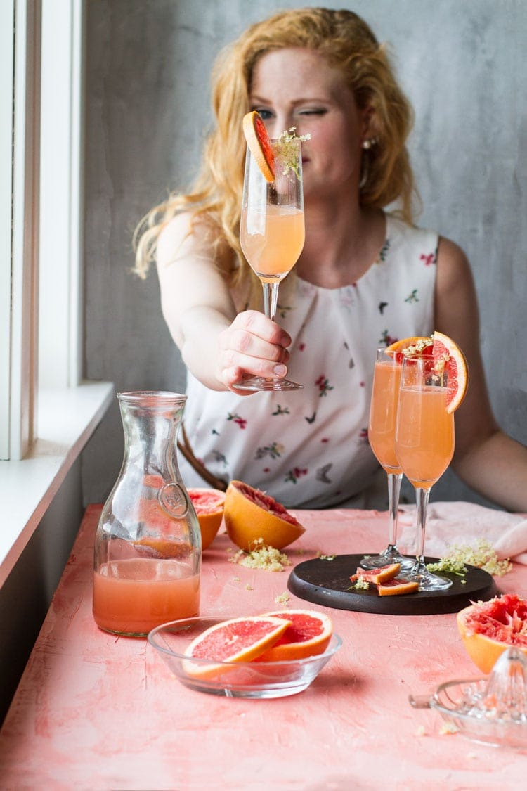 Girl holding up a champagne flute with grapefruit cocktail.