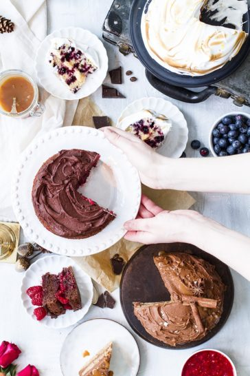 Flat-lay with multiple cakes and hands reaching for the cake stand in the middle.