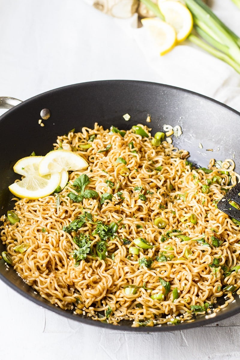 Skillet with fried noodles and green onion.