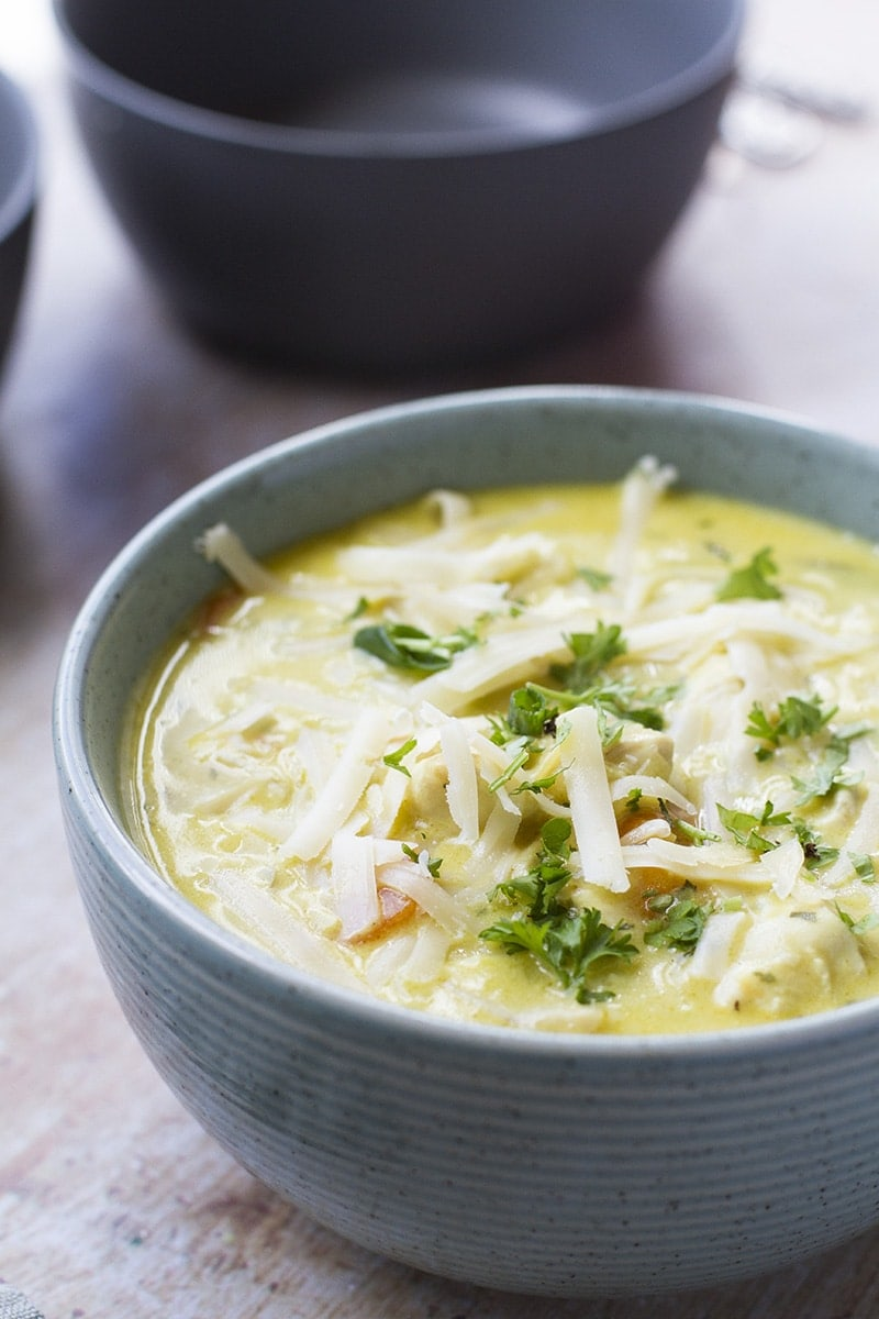 A green bowl with chicken soup that is garnished with shredded cheese and parsley.