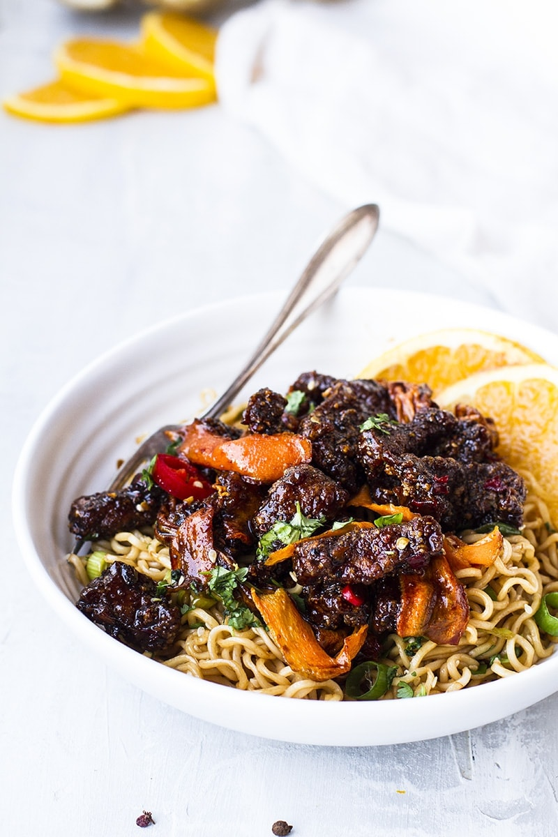 Szechuan beef and carrots over a bed of noodles.